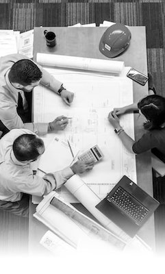 People at a Table Working With Blueprints